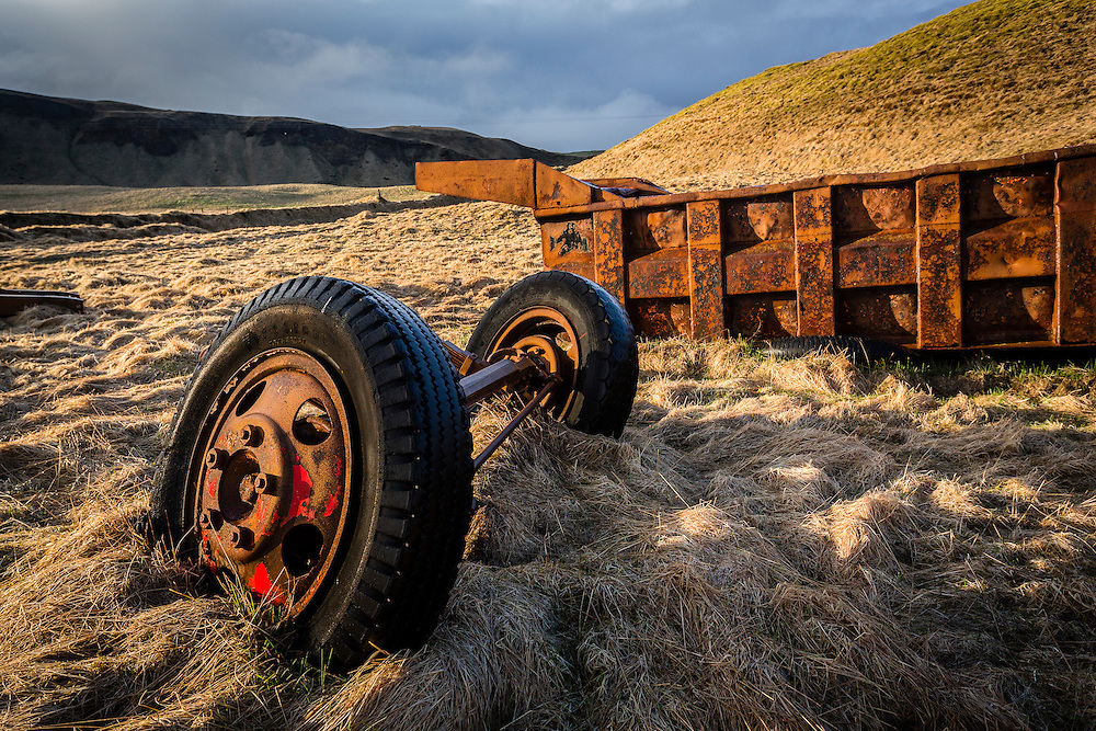 Near the entrance to the farmhouse, assorted vehicle parts are scattered around the landscape