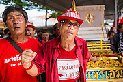 28 APRIL 2014 - BANGKOK, THAILAND:  Thai Red Shirt activists in front of the coffin during the funeral for Kamol Duangphasuk, 45, in Bangkok. Kamol was a popular poet who wrote under the pen name Mai Nueng Kor Kunthee. Kamol had been writing since the 1980s and was an outspoken critic of the 2006 coup that deposed Thaksin Shinawatra. After the 2010 military crackdown against the Red Shirts he went into temporary self imposed exile fearing for his safety. After he returned to Thailand he organized weekly protests against Thailand's Lese Majeste laws, which he said were being used to stifle dissent. Kamol was shot and murdered on April 23. The assailants are still at large but the murder is thought to be political.    PHOTO BY JACK KURTZ