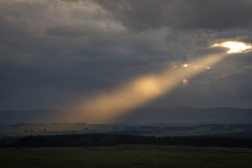 Late afternoon rays of light bursting through clouds over the countryside around The Pentlands range