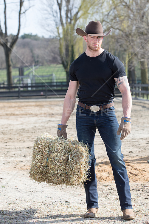 cowboy holding a bale of hay on a ranch