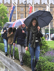 People use umbrellas at Parliament Square in central London.