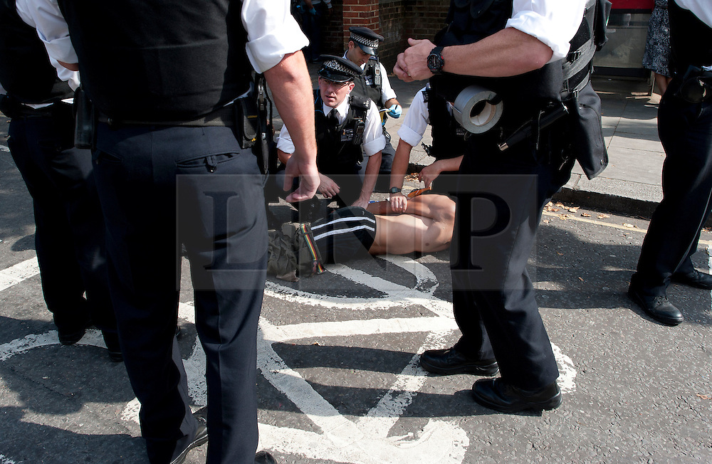 © London News Pictures. 26/08/2013. London, UK. A A man being detained by police on day two of the Notting Hill Carnival in West London on August 26, 2013.  The annual carnival, which is the largest of its kind in Europe, is expected to attract around 1 million people. Photo credit : Ben Cawthra/LNP