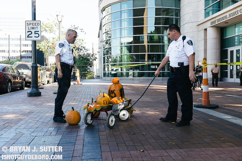Clayton police officers begrudgingly begin to take away a red wagon full of pumpkins left by protesters outside the St. Louis County Justice Center. October 2014. Fujifilm X100s.