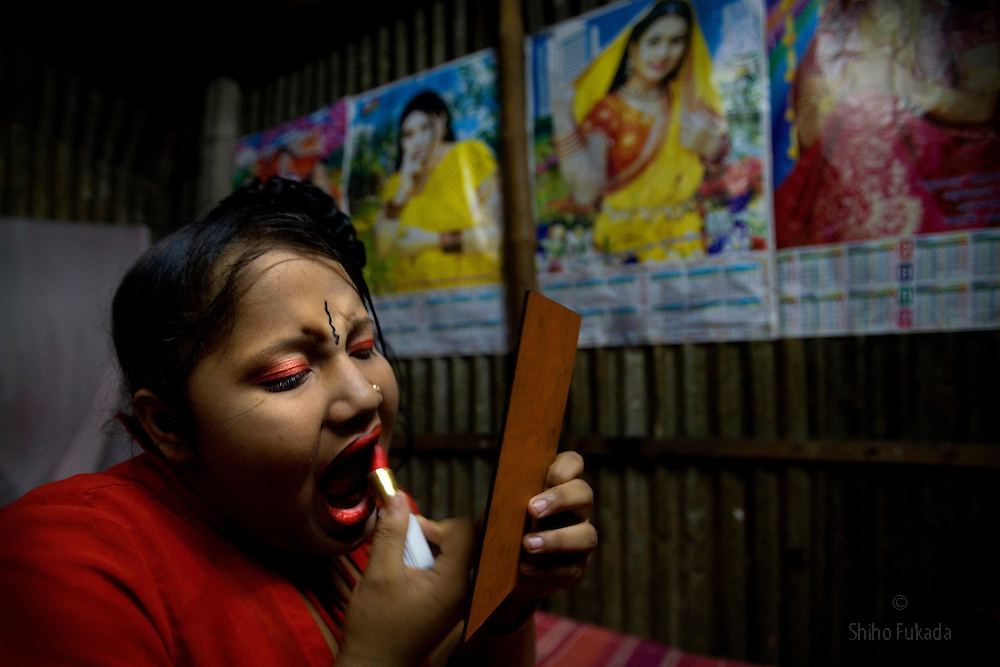 Sex worker Munnie, 15, applies makeup before taking a customer at brothel in Tangail, Bangladesh.