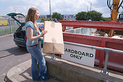 Woman recycling cardboard into a skip at the city tip,
