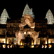 The Angkor Wat complex is lit up at night and forms a spectacular view particular when reflecting in the pools in front of the temple.<br /> <br /> Angkor Wat (Khmer: អង្គរវត្ត) was first a Hindu, later a Buddhist, temple complex in Cambodia and the largest religious monument in the world. The temple was built by the Khmer King Suryavarman II in the early 12th century in Yaśodharapura (Khmer: យសោធរបុរៈ, present-day Angkor), the capital of the Khmer Empire, as his state temple and eventual mausoleum. Breaking from the Shaiva tradition of previous kings, Angkor Wat was instead dedicated to Vishnu. As the best-preserved temple at the site, it is the only one to have remained a significant religious center since its foundation. The temple is at the top of the high classical style of Khmer architecture. It has become a symbol of Cambodia, appearing on its national flag, and it is the country's prime attraction for visitors.<br /> <br /> Angkor Wat combines two basic plans of Khmer temple architecture: the temple-mountain and the later galleried temple, based on early Dravidian architecture, with key features such as the Jagati. It is designed to represent Mount Meru, home of the devas in Hindu mythology: within a moat and an outer wall 3.6 kilometres (2.2 mi) long are three rectangular galleries, each raised above the next. At the centre of the temple stands a quincunx of towers. Unlike most Angkorian temples, Angkor Wat is oriented to the west; scholars are divided as to the significance of this. The temple is admired for the grandeur and harmony of the architecture, its extensive bas-reliefs, and for the numerous devatas adorning its walls.<br /> <br /> The modern name, Angkor Wat, means &quot;Temple City&quot; or &quot;City of Temples&quot; in Khmer; Angkor, meaning &quot;city&quot; or &quot;capital city&quot;, is a vernacular form of the word nokor (នគរ), which comes from the Sanskrit word nagara (नगर). Wat is the Khmer word for &quot;temple grounds&quot; (Sanskrit: वाट vāṭa &quot;&quot;enclosure&quot;).