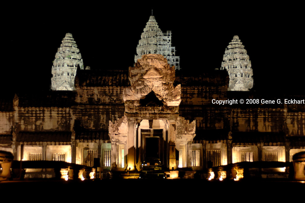 The Angkor Wat complex is lit up at night and forms a spectacular view particular when reflecting in the pools in front of the temple.<br /> <br /> Angkor Wat (Khmer: អង្គរវត្ត) was first a Hindu, later a Buddhist, temple complex in Cambodia and the largest religious monument in the world. The temple was built by the Khmer King Suryavarman II in the early 12th century in Yaśodharapura (Khmer: យសោធរបុរៈ, present-day Angkor), the capital of the Khmer Empire, as his state temple and eventual mausoleum. Breaking from the Shaiva tradition of previous kings, Angkor Wat was instead dedicated to Vishnu. As the best-preserved temple at the site, it is the only one to have remained a significant religious center since its foundation. The temple is at the top of the high classical style of Khmer architecture. It has become a symbol of Cambodia, appearing on its national flag, and it is the country's prime attraction for visitors.<br /> <br /> Angkor Wat combines two basic plans of Khmer temple architecture: the temple-mountain and the later galleried temple, based on early Dravidian architecture, with key features such as the Jagati. It is designed to represent Mount Meru, home of the devas in Hindu mythology: within a moat and an outer wall 3.6 kilometres (2.2 mi) long are three rectangular galleries, each raised above the next. At the centre of the temple stands a quincunx of towers. Unlike most Angkorian temples, Angkor Wat is oriented to the west; scholars are divided as to the significance of this. The temple is admired for the grandeur and harmony of the architecture, its extensive bas-reliefs, and for the numerous devatas adorning its walls.<br /> <br /> The modern name, Angkor Wat, means &quot;Temple City&quot; or &quot;City of Temples&quot; in Khmer; Angkor, meaning &quot;city&quot; or &quot;capital city&quot;, is a vernacular form of the word nokor (នគរ), which comes from the Sanskrit word nagara (नगर). Wat is the Khmer word for &quot;temple grounds&quot; (Sanskrit: 