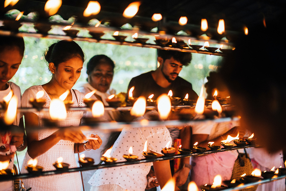 Kandy, Sri Lanka -- January 31, 2018: People gather and light candles at the Temple of the Tooth on Poya Day.