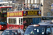 Open-topped sightseeing bus travelling in Trafalgar Square, downtown London city centre, England, United Kingdom