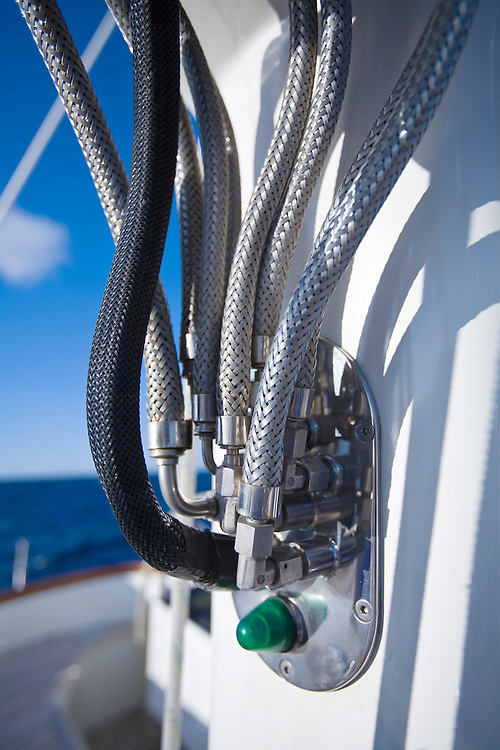 A tangle of hydraulic hoses leads into the mast of a megayacht. Most large sailing yachts have such large equipment that much of it is operated by computer operated hydraulics.