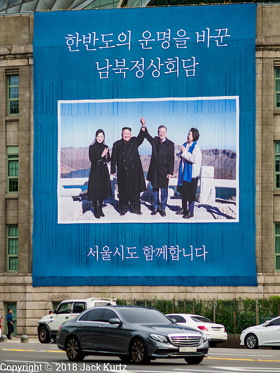 09 OCTOBER 2018 - SEOUL, SOUTH KOREA: People walk past a large sign hanging from the Seoul public library marking the September summit meeting between North Korean lead Kim Jong-un (center left) and his wife, Ri Sol-ju (left) and South Korean President Moon Jae-in (center right) and his wife,  Kim Jung-sook.   PHOTO BY JACK KURTZ