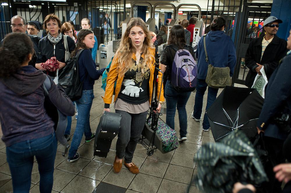 Natalie Gelman, 25, Saengerin und Songwriter mit Guitarre, begeistert mit Talent und Ausstrahlung. Sie ist offiziele Musikerin von 'Music Under New York'. Hier beim Verlassen der Columbus Circle Ubahn Station...Jedes Jahr im Mai laden die Betreiber der New Yorker Subway (MTA) ca 60 Musiker und Gruppen zu einem Wettberwerb im Grand Central Station ein. Die Gewinner duerfen ganz legal an ihnen zugeteilten Orten im Ubahn System auftreten. Viele unangemeldete  und selbst organisierte Musiker jeder nur erdenklichen Musikrichtung spielen zudem in fast jeder wichtigen Ubahnstation. Die Angst vor der Polizei ist dabei gering, selten gibt es eine Verwarnung und noch seltener ein Bussgeld. Meist wird einfach der Ort gewechselt falls es Probleme gibt...Natalie Gelman, 25, singer songwriter, draws crowds with her talent and enthusiasm. She is a participant of 'Music Under New York'. Here she is leaving her spot at Columbus Circle after a 3 hour performance...MTA (Metropolitan Transportation Authority) .Music Under New York.Auditions.Every Spring, Music Under New York (MUNY) presents a day of auditions in Grand Central Terminal to review and add new performers to the MUNY roster. This year, MUNY held its annual auditions in May on the Northeast Balcony of the Grand Central Terminal. .In addition legions of non-official musicians play in New Yorks subway stations and on platforms. One can find every thinkable style and instrument underground. ..Foto: Stefan Falke.