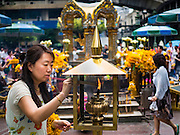 16 AUGUST 2016 - BANGKOK, THAILAND: A woman lights incense at Erawan Shrine one year after the shrine was bombed in the worst international terrorist attack in Thai history. On 17 August 2015, a bomb was set off at the Erawan Shrine, a popular tourist attraction and important religious shrine in the heart of the Bangkok shopping district. According to the Royal Thai Police  20 people were killed in the bombing and 125 injured. Thai Police arrested an alleged Uighur extremist for the bombing. The case against him is still pending in Thai courts. The shrine was repaired, rededicated and reopened to the public on 4 September 2015.      PHOTO BY JACK KURTZ