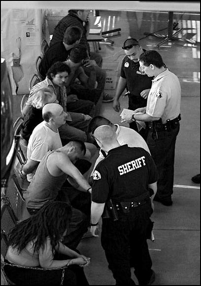 Michael Stenerson / Staff Photographer.The Student Activities Center at Victor Valley College was turned into a booking station Friday as law enforcement officers prepare prisoners for departure to jail during a saturation sweep. Over 100 law enforcement officers spread out over Apple Valley and Hesperia to try and round up criminals.
