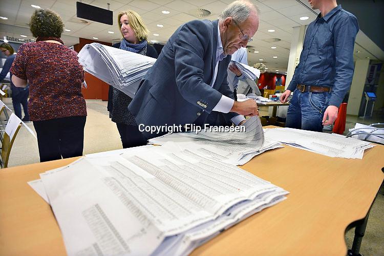 Nederland, Nijmegen, 19-3-2014 Bij het stembureau in het informatiecentrum van de gemeente wordt om 21.00 uur de stembus geleegd en de stemmen, stembiljetten, geteld met extra vrijwilligers. Per partij wordt een stapel gemaakt. Het tellen van de stemmen is openbaar, maar er komt maar zelden iemand naar kijken. Foto: Flip Franssen