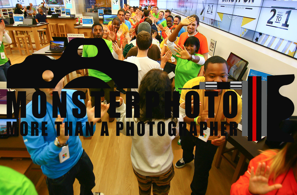 Microsoft store associates greets the first customers with high-fives as the Microsoft store opens to the public Saturday, Sept. 29 2012, at Christiana Mall in Newark DE..