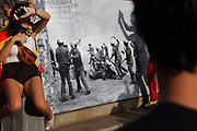 Festival goers wearing the catalan flag, celebrating catalan nationalism, in front of a photograph of police brutality, on Diada, or La Diada Nacional de Catalunya, Catalonia's National Day, on 11th September 2018, Barcelona, Catalonia, Spain. 2018 saw the largest Diada march ever, organised by the Catalan National Assembly, with a million people taking to the streets, supporting secession and the reinstatement of the unrecognised Catalan Declaration of Independence after the referendum of 2017. Picture by Manuel Cohen