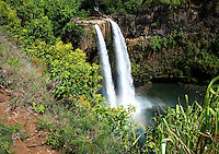 Hawaii, South Pacific.  Waterfall tumbling into a clear pool, surrounded by dense greenery.