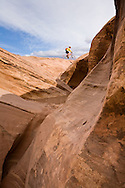 Bill Boardman rides near the lip of a slot canyon as seen from the White Rim Trail in Canyonlands National Park, Utah.