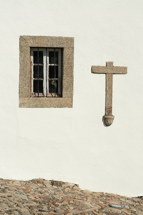 A window in an wall of an old Alentejo church with a stone cross on the wall