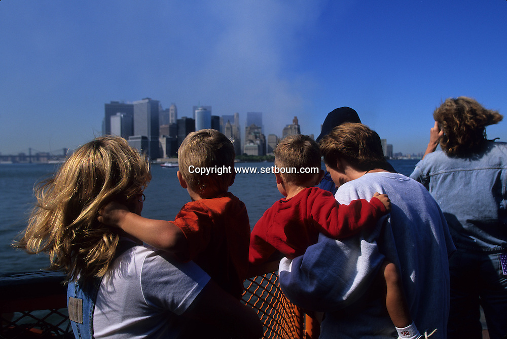 New York.  family watching The destroyed skyline view from Staten island  Ferry. after the terorist attack on world trade center towers in Manhattan  New york  Usa /   famille regardant Le skyline detruit vu depuis le staten island ferry . Apres l'attaque terroriste sur les tours du world trade center a Manhattan  New york  USA