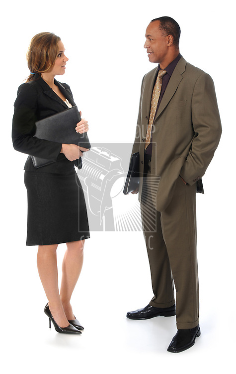 A professionally dressed man and woman standing against a white background while talking to each other