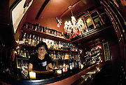 "Masayuki Era stands behind the bar at Albatross G in Golden Gai, Shinjuku, Tokyo. Customers wander past bars in the Golden Gai district of Shinjuku, Tokyo, Japan. Golden Gai was once notorious as one of Tokyo's most frequented red light districts and began life immediately after World War II as an extension of the black market area around Shinjuku station, which also includes the little alley of bars and eateries known locally as Shonbenyoko-cho. Due to its low rents and relative seclusion, the area was a magnet for all sorts of illegal activity and was an extension of what is known in Japan as the ""mizu shobai"", which is often rendered in English as the ""floating world"" but literally means the the ""water business"". During the period immediately following Japan's occupation by the Allied Forces, illegal activities, such as prostitution, in the area was outlawed, and the tiny establishments were taken over by proprietors, mostly women known as ""mama-san"",  who dedicated their business energy into selling drink and cheap but good food.  Over 200 watering holes are now in operation along the maze of alleys, largely occupied by artisans, writers and musicians."
