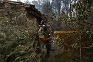 LEIRIA, PORTUGAL - JUNE 19:  A Portuguese soldier checks the area and empty properties for possible human remains after a wildfire took dozens of lives on June 19, 2017 near Castanheira de Pera, in Leiria district, Portugal. On Saturday night, a forest fire became uncontrollable in the Leiria district, killing at least 62 people and leaving many injured. Some of the victims died inside their cars as they tried to flee the area.  (Photo by Pablo Blazquez Dominguez/Getty Images)