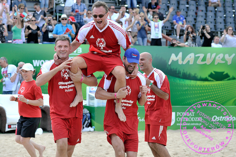 Sebastian Swiderski (L) and Pawel Pake (R) hold of Cezary Pazura (C) while exhibition match of Special Olympics Poland during Day 7 of the FIVB World Championships on July 7, 2013 in Stare Jablonki, Poland. <br /> <br /> Poland, Stare Jablonki, July 07, 2013<br /> <br /> Picture also available in RAW (NEF) or TIFF format on special request.<br /> <br /> For editorial use only. Any commercial or promotional use requires permission.<br /> <br /> Mandatory credit:<br /> Photo by &copy; Adam Nurkiewicz / Mediasport