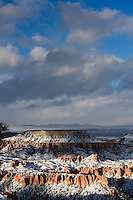 Late afternoon sun peaks through winter clouds and highlights sections of Bryce Canyon National Park, Utah.