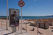 A ironic No Dogs sign next to a police ad for abandoned animals on the beach at Estoril near Lisbon, Portugal.