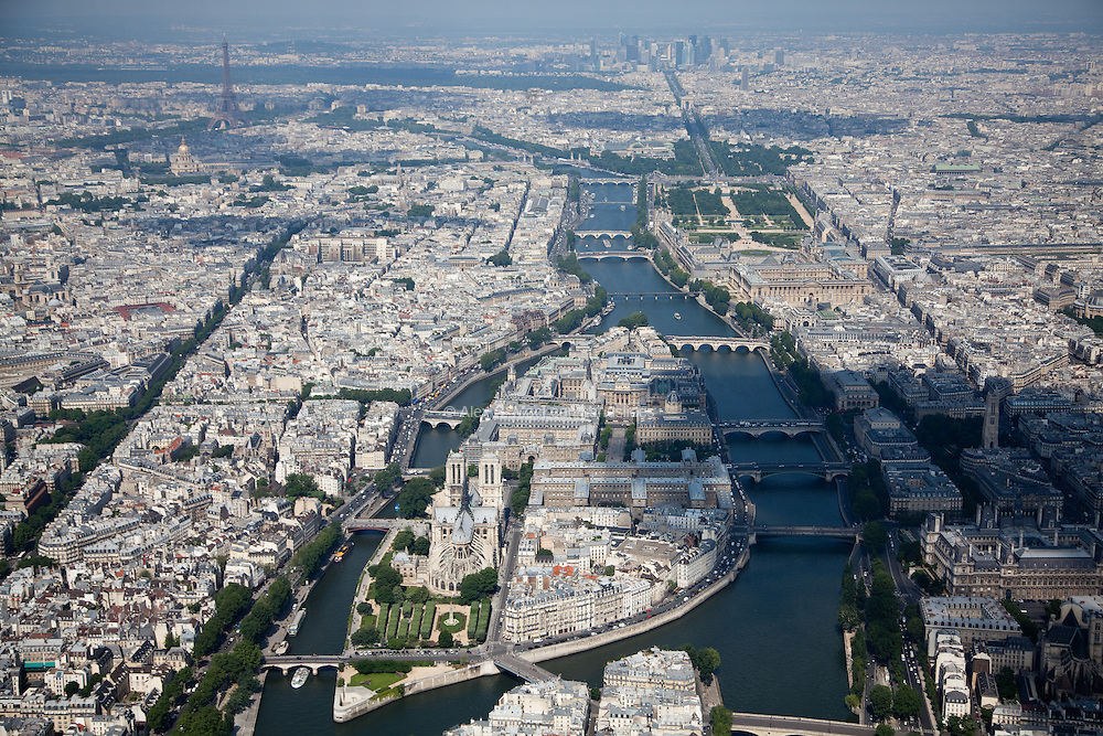 Looking down the Left and Right Banks of the Seine with Ile Saint-Louis and Ile de la Cité, and Notre Dame and numerous bridges linked to the city with the Eiffel Tower and La Defense in the background.