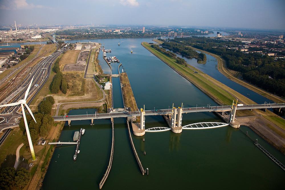 Nederland, Zuid-Holland, Botlek, 19-09-2009; Functioneringssluiting Hartelkering, de waterkering in het Hartelkanaal  wordt een maal per jaar, voordat het stormseizoen begint, getest. Tijdens  het sluiten van de kering ligt alle scheepvaartverkeer naar de Rotterdamse haven stil. .Links in de achtergrond Botlek en olieraffinaderij, rechts Hoogvliet en Oude Maas. Rechts de dijk die deel uit maakt van de Europoortkering..De kering sluit normaal gesproken alleen bij dreigende stromvloed en bij een waterstand van 3 meter of meer boven NAP. De kering, onderdeel van de Deltawerken, vormt samen met de Maeslantkering  de Europoortkering en beschermt Rotterdam en achterland bij extreme waterstanden. .Netherlands, Rotterdam harbour. Aerial view of one of the two storm surge barriers. This barrier, the Hartelkering  in the Hartel canal, together with the greater nearby  Maeslant barrier (in the New Waterwy), are tested during the so-called functioning closure, taking place one a year before the storm season begins. The waterway and canal, leading to the Port of Rotterdam, are closed during the test..luchtfoto (toeslag), aerial photo (additional fee required).foto/photo Siebe Swart