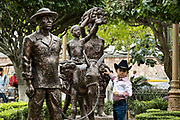 A young Mexican boy poses by a statue honoring the indigenous Totonac people in the Plaza Central Israel Tellez Park in Papantla, Veracruz, Mexico.