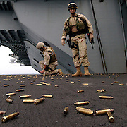 Onboard USS Harry S. Truman (CVN-75) .Information Technician First Class Allen Schneider and Boatswain's Mate Chief Charles Phillips are surrounded by a sea of empty shells after participating in a small arms exercise aboard the Nimitz-class aircraft carrier USS Harry S. Truman.  Both Schneider and Phillips are members of Explosive Ordnance Disposal Mobile Unit SIX, Detachment TEN (MU6 DET10) out of Charleston, South Carolina.