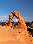 View of Delicate Arch with the La Sal Mountains in the background, nearing sunset; Arches National Park, Moab, Utah, USA.