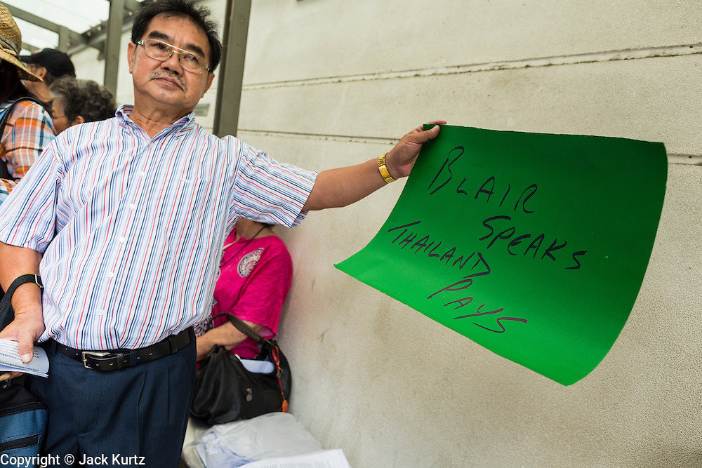 27 AUGUST 2013 - BANGKOK, THAILAND:      A Thai man protester holds up a sign protesting against the fee allegedly paid to Tony Blair to bring him to speak in Thailand. About 25 people, including at least two British citizens, picketed the British embassy in Bangkok Tuesday morning. They were protesting against former British Prime Minister Tony Blair, who is expected to speak to a political reform commission established by Thai Prime Minister Yingluck Shinawatra. The protest leaders were invited in to the Embassy grounds to speak to representative of the British government. The protest disbanded afterwards. No one was arrested during the protest, which lasted a little over an hour. The Thai government has denied paying Blair his usual fee of about $800,000 (US).  PHOTO BY JACK KURTZ