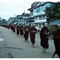 A long line of Burmese Monks moves through the streets of Bago, the ancient capital of Burma, in a daily round to collect food and bless the people, a few days after the strong repression..Many monks in their twenties are now the target of the persecution and repression of the military dictatorship in Burma. Monday October 8,2007. Bago, Myanmar (Burma)