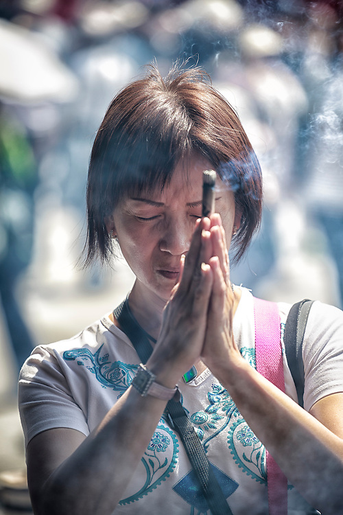 A woman prays with incense at Sensoji temple.