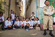"""04 FEBRUARY 2013 - PHNOM PENH, CAMBODIA:  A Cambodian police officer stands next to Cambodians sitting in an alley near the National Museum waiting for the cremation of King-Father Norodom Sihanouk to begin. Norodom Sihanouk (31 October 1922- 15 October 2012) was the King of Cambodia from 1941 to 1955 and again from 1993 to 2004. He was the effective ruler of Cambodia from 1953 to 1970. After his second abdication in 2004, he was given the honorific of """"The King-Father of Cambodia."""" Sihanouk died in Beijing, China, where he was receiving medical care, on Oct. 15, 2012.   PHOTO BY JACK KURTZ"""