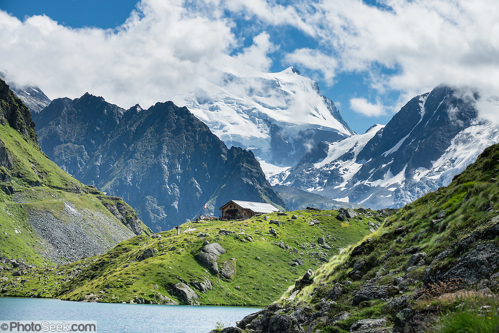 The peaks of Grand Combin (4314 metres / 14,154 ft at center) and Combin de Corbassière (right) rise above Lake Louvie in the Pennine/Valais Alps, Switzerland, Europe. Optionally stay overnight in dorms at Cabane de Louvie. The dramatic Chamois Path (Sentier des Chamois) starts at La Chaux ski lift and ends at Fionnay PostBus. Cross Col Termin (2648m/8688 ft) in Haut Val de Bagnes nature reserve and descend to Lake Louvie via 1800s stone barns to the north, then to Fionnay (640 m up, 1415 m down in 8.5 hours).