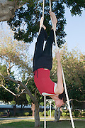 Female acrobat on a trapeze upside down
