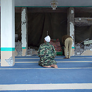 Men pray during Ramadan in a mosque destroyed my the earthquake.