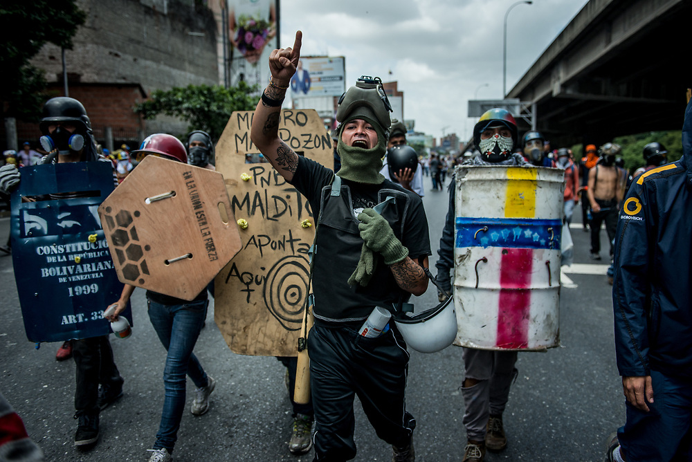 CARACAS, VENEZUELA - MAY 26, 2017:  Anti-government protesters using homemade shields  take control of the Francisco Fajardo highway.  The streets of Caracas and other cities across Venezuela have been filled with tens of thousands of demonstrators for nearly 100 days of massive protests, held since April 1st. Protesters are enraged at the government for becoming an increasingly repressive, authoritarian regime that has delayed elections, used armed government loyalist to threaten dissidents, called for the Constitution to be re-written to favor them, jailed and tortured protesters and members of the political opposition, and whose corruption and failed economic policy has caused the current economic crisis that has led to widespread food and medicine shortages across the country.  Independent local media report nearly 100 people have been killed during protests and protest-related riots and looting.  The government currently only officially reports 75 deaths.  Over 2,000 people have been injured, and over 3,000 protesters have been detained by authorities.  PHOTO: Meridith Kohut