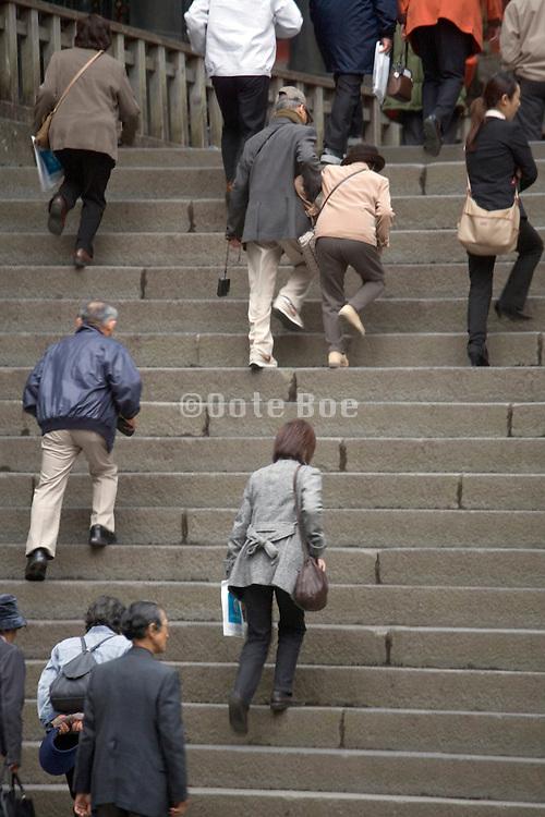 people walking up large stairs