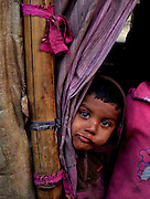 03-years-old Muhammad Yunus looks out of his makeshift camp room at the outskirts of Delhi State of India. More than 10,000-numbers of Burmese Rohingya Muslim refugee took shelter in Indian (Hyderabad) Andhra Pradesh, (Mewat) Haryana, (Kanchankunj) Delhi and Jammu States after ethnic strife between Rohingya Muslims and Buddhists that had been started since 1940s. Still so many peoples of aforesaid community have been living at various refugee camps in Myanmar, Bangladesh and India chiefly. Rohingya Muslims of Buthidaung, Rathedaung and Sittwe of Rakhine (formerly, Arakan) State, who ran away from Myanmar (that is, Burma) to Bangladesh to India and others South-Asian countries to escape socio-political-religious violence. (Photo/Shib Shankar Chatterjee)
