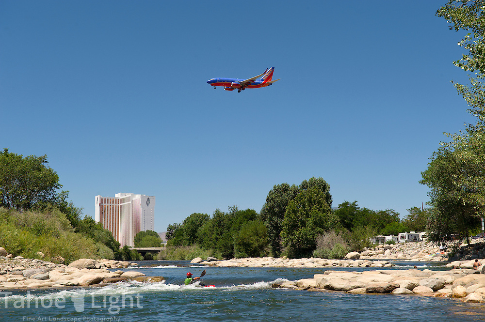 A plane flies overhead as people play in the newly constructed whitewater park on the Truckee river in Sparks, Nev., next to Reno. The Reno whitewater park has been a major draw for local families and Sparks hopes to emulate their success.  (AP Photo/Scott Sady)