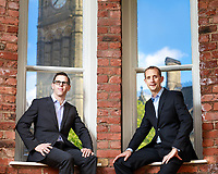 Business partners sat on window sill with view of Manchester Town hall behind. Taken in cool office with exposed red bricks