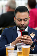 A gent placing his online bets on the mobile app at York Racecourse, York, United Kingdom on 26 May 2018. Picture by Mick Atkins.