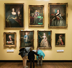 Visitors looking at old portrait paintings at the German History Museum in Berlin, Germany